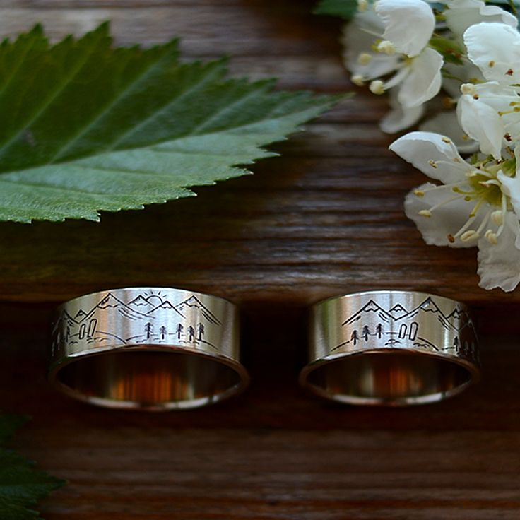 """Широкие обручальные кольца с изображением """"Горы""""по эскизам заказчика. Эти кольца отличаются тем, что имеют двусторонний рисунок. С одной стороны - зенит в горах, сноуборды влюбленной пары в сугробе, а с другой стороны - заказ на пляже с дорожкой света на воде. Ширина колец 8 и 8 мм. Белое золото."""