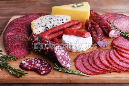 Sortido de enchidos e queijos na tábua e fundo de mesa de madeira — Imagem Stock #61894907