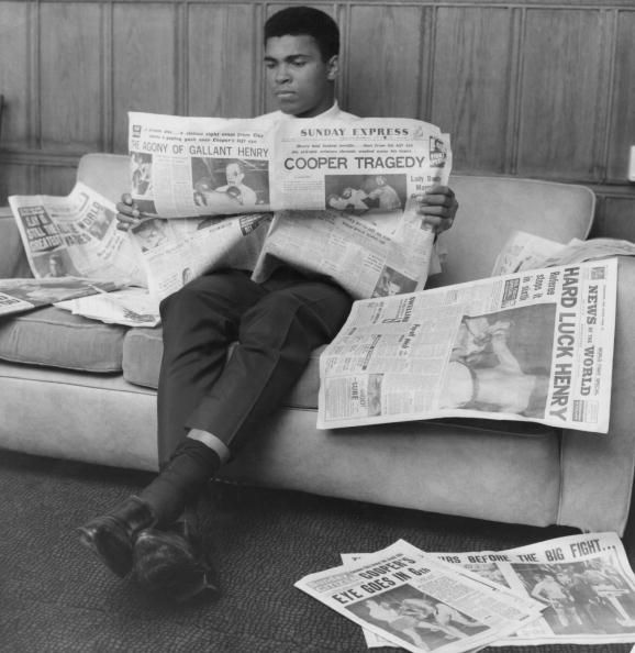 Boxer Cassius Clay pictured reading the Sunday Express newspaper London Great Britain 23 May 1966 The headline on the newspaper reads 'Cooper...