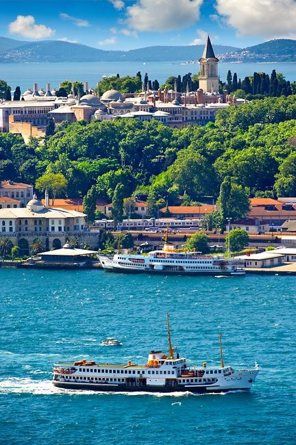 The Topkapi Palace on Sarayburnu or Seraglio Point with a ferry and the banks of the Golden Horn in the foreground, Istanbul Turkey.