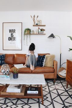 Midcentury boho living room with leather couch, open shelves, and wall art. | New Darlings
