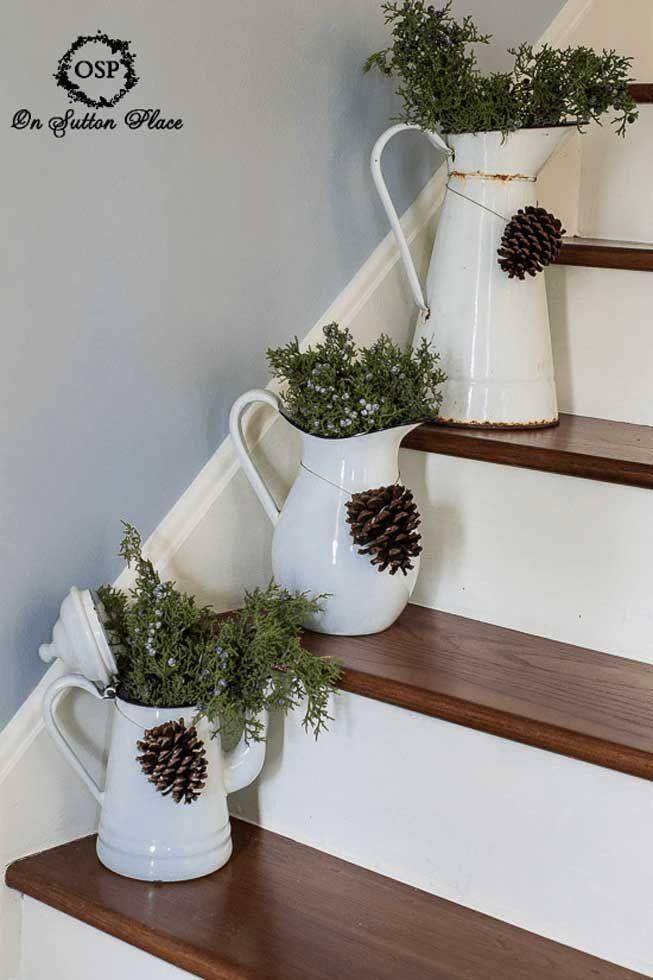 Pine cones strung around rustic, decorative pitchers