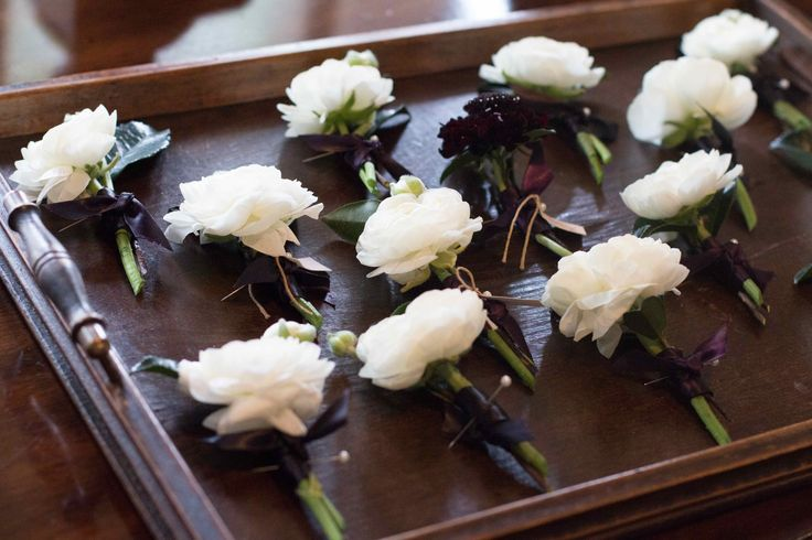white ranunculus boutonnieres for the groomsmen and one of burgundy scabiosa for the groom arrive on a vintage wood tray.