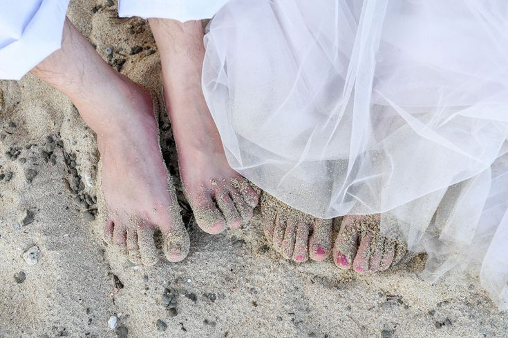 Feet of the bride and groom in the white sand  at Paradise Cove island resort in Fiji by Anais Photography