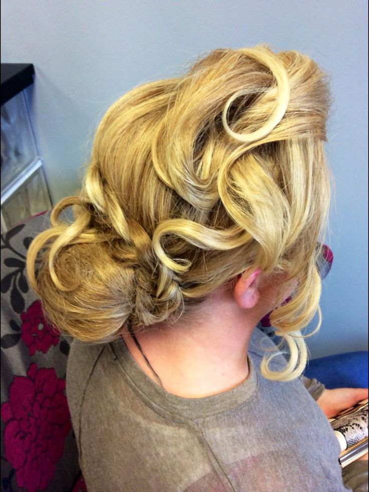 an elegant upstyle with a low bun and a plait with sweeping curls framing the face. Perfect wedding style