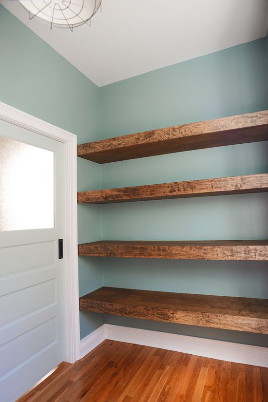 Gorgeous reclaimed wood floating shelves along the entire length of a small wall.