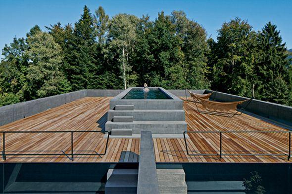 Donnant sur le lac de Lucerne, située dans une zone boisée entre chênes, bouleaux et châtaigniers, ce monolithe impressionne par sa taille et sa forme géométrique. Composée de deux étages, la maison dispose d'une façade en béton gris foncé et d'un surplomb en bois avec piscine et terrasse.