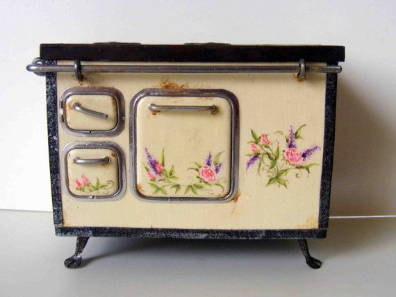 This type of kitchen stove is known as sparherd in Middle- or East-Europe. This miniature is absolutely handmade. The stovepipe is not fixed, so you can rotate or shorten it for the right attaching onto the chimney wall. The doors dont open. The flower patterns are hand painted. Size with the rail: 90x76x60mm (width, height, depht), plus the pipe.  This item is in one inch scale.  This miniature is for collectors and not recommended under age of 12.