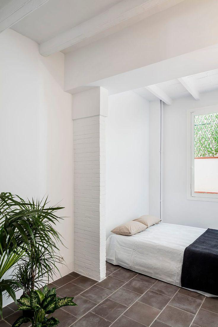 Quarto reformado, ambiente com piso original cinza escuro, plantas em vasos e paredes brancas. Apartamento Minimalista em Barcelona por RAS Studio