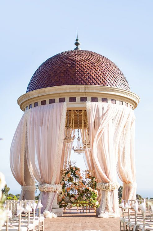 A rotunda is transformed with dreamy pink linens bound by gorgeous floral wreaths and crystal chandeliers. Click to view the full wedding gallery.