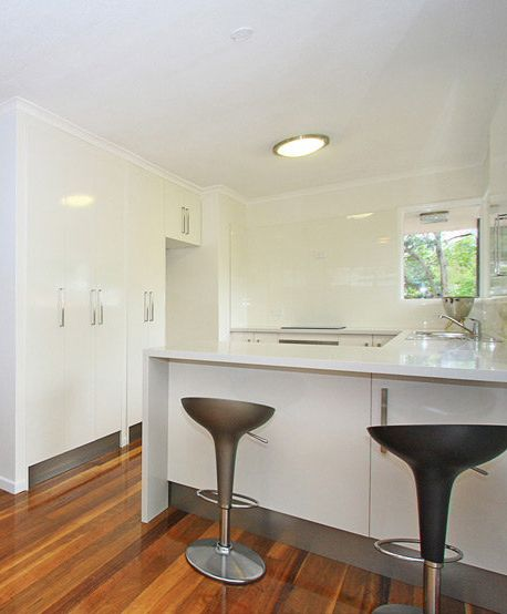 Kitchen Solutions - white on white gloss kitchen with stainless steel kickboards in Indooroopilly