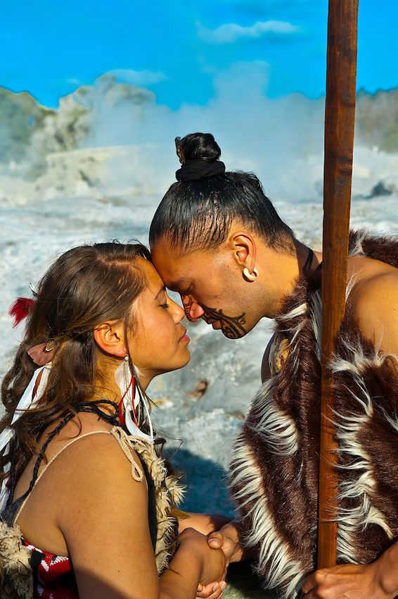 A Maori man with ta moko (facial tattoo) and woman doing hongi (traditional Maori greeting) with the Pohutu Geyser behind, Te Puia (New Zeal...