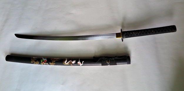 Gekromd zwaard in Japanse Samurai-stijl /Katana (replica) - Azie - 21 eeuw  Zwaard licht gekromd en van puntvormig gehard staal.Het heeft één snijvlak. Dit zwaard dient ter decoratie en is niet scherp. Het zwaard is opgebouwd volgens Japanse traditie en versierd met diverse Japanse motieven.Het heft (Menuki) is ruitvormig omwikkeld met zwarte bandage. De schede (Saya) is gemaakt van bamboe fijn beschilderd met een traditionele Japanse afbeelding en eveneens voorzien van een traditionele…