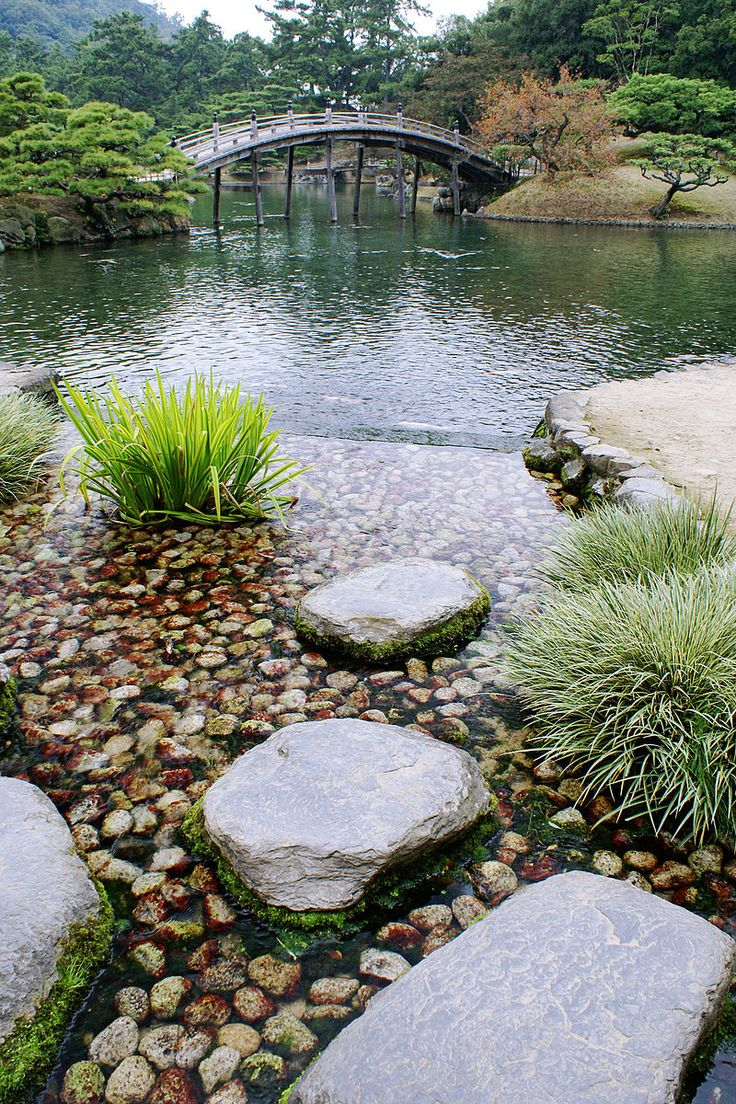 Japanese bridge in garden as well as pond with sabi stones