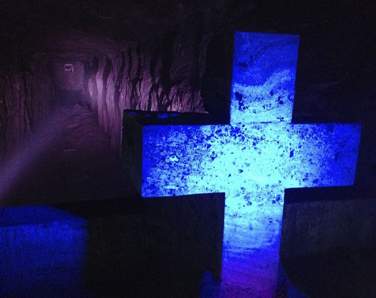 A cross made from salt in front of a deep pit illuminated by purple light at the Zipaquira Salt Cathedral, about an hour away from Bogota, Colombia.
