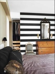 En känsla av art deco genomsyrar sovrummet, med dess svarta och orientaliskt mönstrade kuddar,  svart-vitrandiga tapet från Björklund&Wingquist och kviltade sammetsöverkast. Sekretär från 1700-talet. Stol i Louis seize-stil och spegel i karljohansstil, båda 1800-tal. Allt är arvegods. Bakom väggen ryms en välplanerad walk-in-closet.