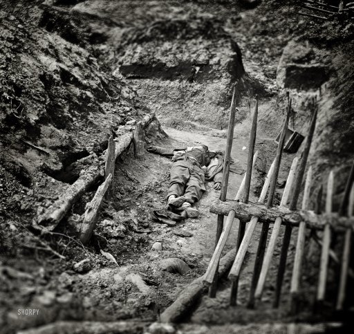 "April 3, 1865. Petersburg, Virginia. ""Dead Confederate soldiers in trench beyond a section of chevaux-de-frise."""