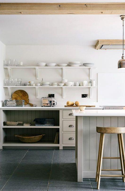 White shelves, bead board, kitchen island, white china, wooden stool, round cutting board