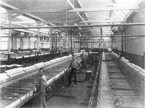 Interieur grofspinncrij Gebr. van Heek, Enschede, circa 1895. De spinners - mannen - hadden elk twee handlangers, aanlappers genaamd. Enschede werd in de tweede helft van de negentiende eeuw hét centrum van de katoenspinnerij in Nederland. Zowat de helft van de spincapaciteit in Nederland was hier geconcentreerd. Voor een deel ging het om geïntegreerde ondernemingen, waarbij de spinnerij een onderdeel vormde van een totaal textielbedrijf, zoals hier het geval is.