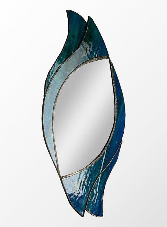 Il sagit dun simple mais superbe design miroir symétrique créée avec belle verre texturé de bleu-vert. Les morceaux de miroir et verre souillé sont toutes individuellement taillés à la main et assemblés à laide de la technique de clinquant de cuivre traditionnel. Cette méthode a été tout dabord utilisée dans la fin des années 1800 par les Studios de Tiffany aux Etats-Unis pour créer leur célèbre Tiffany lampes.  Les courbes tourbillonnantes du dessin ou modèle rappellent lère Art Nouveau…