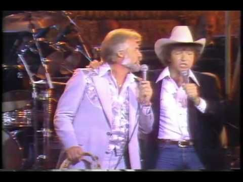 Mac Davis singing his song 'Hard to be a Humble' live during a Kenny Rogers concert in the 80's.