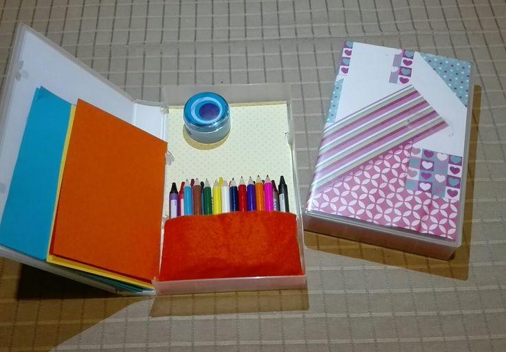 Bezigheidstherapie in de auto, recyclage van oude videodoosjes.  Benodigdheden: gekleurd papier, alleslijm, vilt, schaar, potlood.  Knip de uitsparingen van de doos uit.  (kan per doos verschillen!) Stukje vilt achteraan vastkleven, zakje maken. Buitenzijde versieren, papiertjes op maat knippen om erin te stoppen.  Veel plezier!