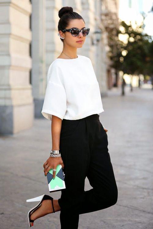 Comprar ropa de este look:  https://lookastic.es/moda-mujer/looks/top-corto-pantalon-de-pinzas-sandalias-de-tacon-gafas-de-sol-pulsera/12055  — Gafas de Sol Negras y Blancas  — Top Corto Blanco  — Pulsera Plateada  — Sandalias de Tacón de Ante Blancas y Negras  — Pantalón de Pinzas Negro
