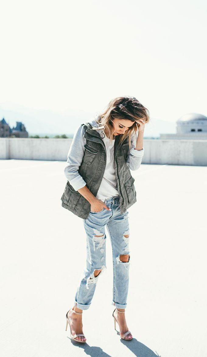 cute and casual in an olive utility vest over grey sweater + light wash denim + neutral heels