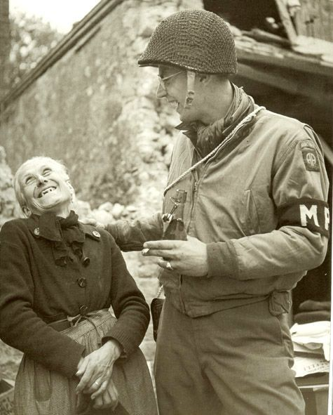 With a bottle of cider in hand, a member of the Military Police of the 82nd Airborne jokes with an old woman.