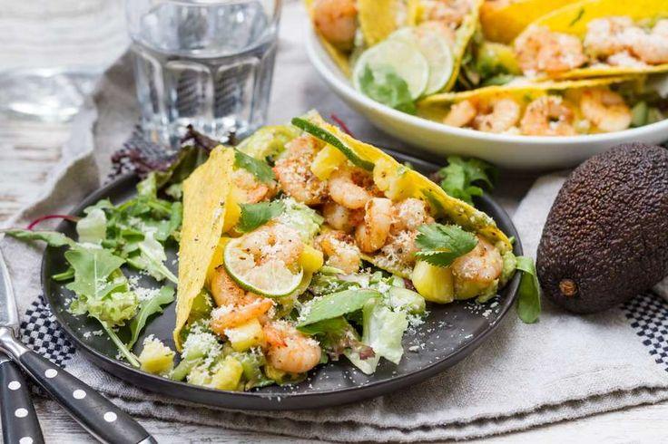 Recept voor taco's voor 4 personen. Met zout, olijfolie, peper, taco schelp, garnaal, komkommer, avocado, ananas, slamelange, parmezaanse kaas en limoen