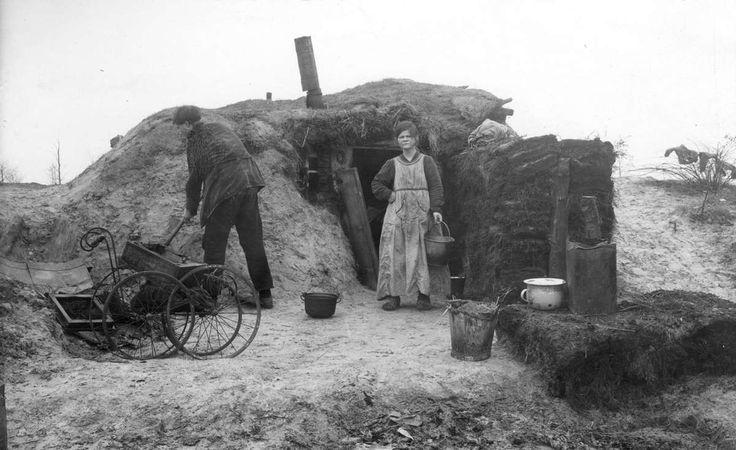 Bittere armoede in een plaggenhut in de Drentse Venen nabij Erica, 1926. Buiten staan emmers, een po, een pan en een roestig onderstel van een kinderwagen.