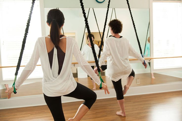 Rows of bungee cords hang from the ceiling in the studio at Pilates Loft…