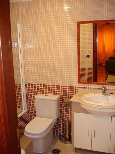 Reforma Baño Integral:Baño rojo y crema Reforma integral de baño, como revestimiento se