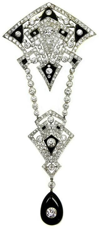 Early Art Deco openwork diamond and onyx corsage brooch, c.1920, of geometric design formed by two graduated kite motifs, millegrain set with lines of diamonds and inset with onyx sections, the smaller kite hung below on two detachable lines of articulated collet diamonds, the whole suspending a polished pear shaped onyx inset with a round brilliant cut diamond.