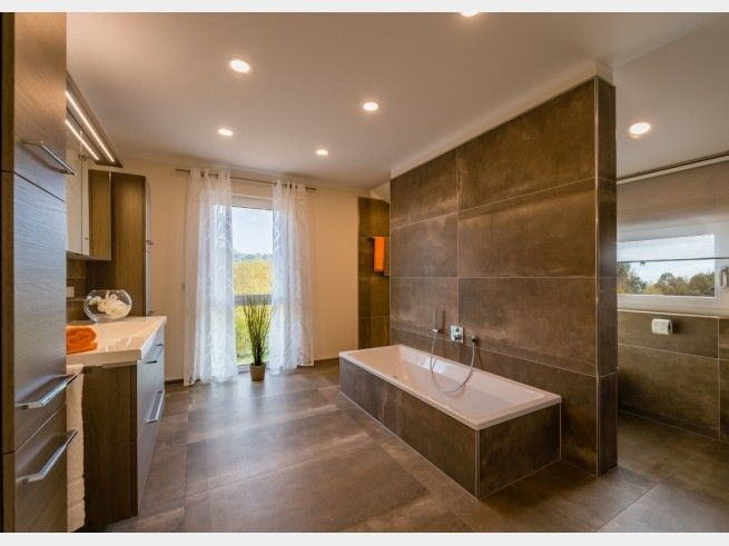 Elegant Ger umiges Badezimmer mit Badewanne und Raumtrennung im Musterhaus G teborg von RENSCH Haus