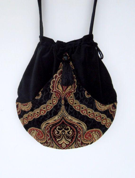 Borsa perfetta per la signora Spirita libera. Ha la tasca frontale, che è un arazzo tessuto nero, rosso e crema. Larco ha una nappina. La borsa stessa è un velluto di cotone nero. È una disegnare stringa borsa con quello fuori tasca per tutto lessenziale immediato a vostra disposizione. Il cinturino è 52 circa La borsa misura 14 lungo e 14 esso è più ampia.