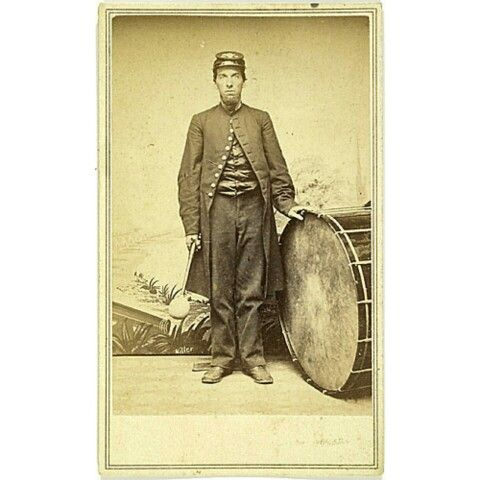 "CDV of New Hampshire Civil War Bandsman with Bass Drum, with graphic ""Lady Liberty"" imprint of J. Sidney Miller, Nashua, N.H. with name advertised at bottom of painted canvas. An unidentified infantry musician with NHV brass insignia and illegible single digit number on forage cap. He holds a drum beater posed next to a massive bass drum exhibiting well-used heads. The bass drum was not normally allocated to field music but rather the combined regimental or brigade band. At the start of the…"