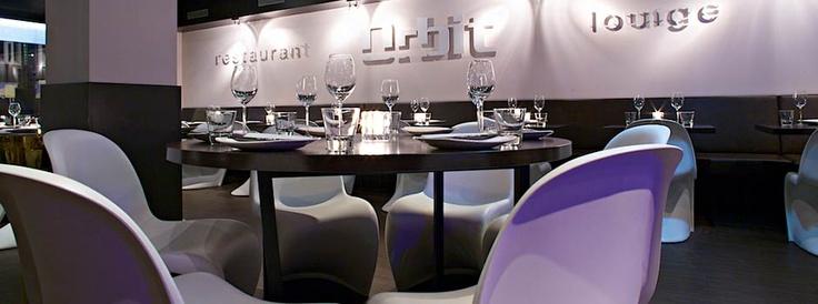"""Orbit Restaurant & Lounge heeft een vestiging in Amsterdam op loopafstand van de RAI. Uit verschillende Aziatische landen hebben zij de lekkerste kleine hapjes geselecteerd en op de kaart gezet. Het woord """"Lounge"""" geeft gelijk een sfeerverwijzing dat door Voskuilen Interieur is opgepakt en omgezet in een interieurontwerp. Als Aziatisch restaurant is er wel een verwijzing naar het oude oosten maar de inrichting is modern en westers."""