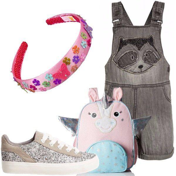Salopette in jeans con pantaloni corti. Sneakers basse con pailettes argentate e suola in gomma. Zaino a forma di unicorno color argento, rosa e azzurro. Il cerchietto decorato con fiori e farfalle dona un tocco di colore.