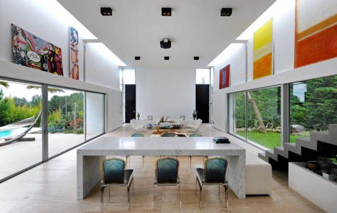 Mramorový jídelní stůl navržený a vyrobený na míru je doplněn plastovými židlemi s aplikací obrazu čalounění ve stylu Ludvíka XVI. Vysoké stěny dekorují ohromné prosklené plochy, v nichž je vidět místní vegetace jako na velké obrazovce, a nad nimi jsou zavěšené tři obrazy Marka Rothka, představitele abstraktního expresionismu, a obrazy od současné výtvarnice Anne de Renzis