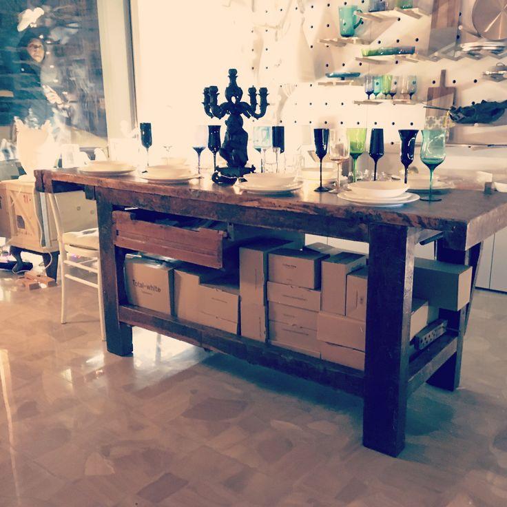 tavolo falegname restaurato, con piatti e bicchieri bitossi e selettiva