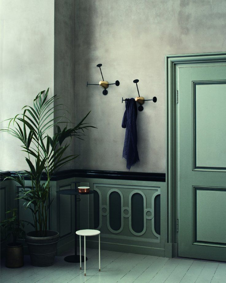 Green panelling and brass wall hooks