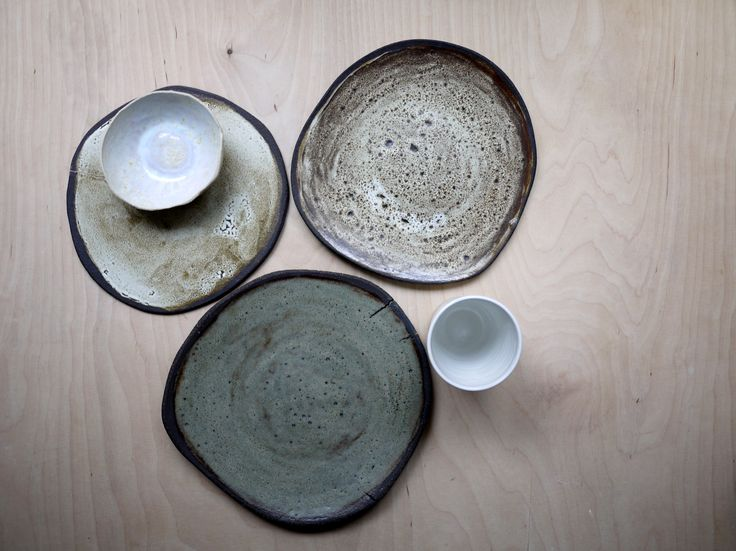 Collection of rusty handmade ceramic tableware: plates and bowls in off white grey tones.