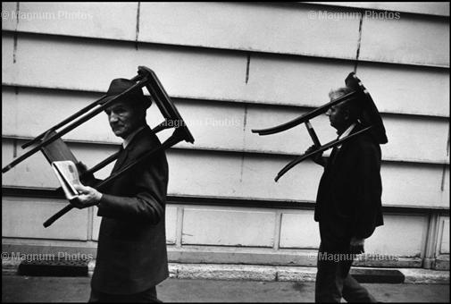 Richard Kalvar  Men walking with tables on heads.