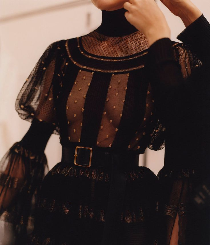 A black sheer lace dress with intarsia polka dots and voluminous sleeves is photographed during fittings in the atelier.