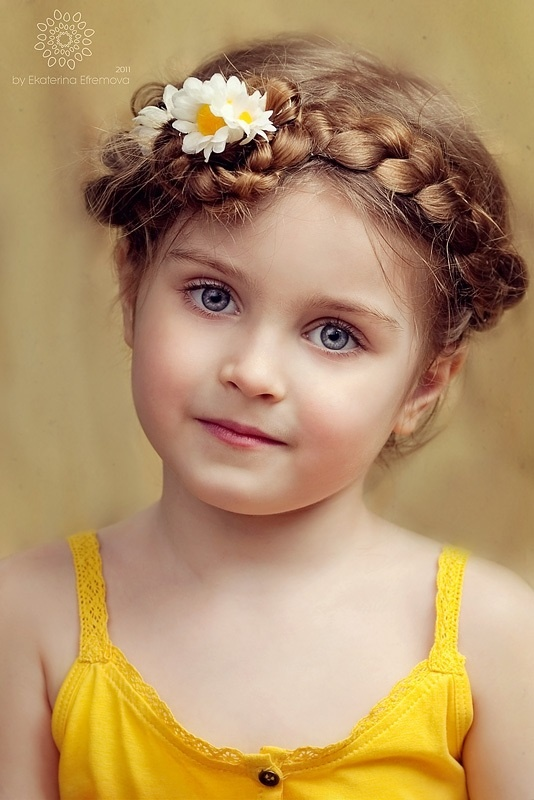 Precious Child. LOVE the hair. Doesn't look easy. Photo was taken in 2011. The photographer's name is faint, top left.