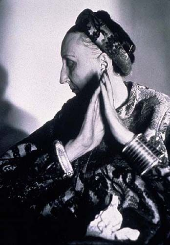"""Edith Sitwell wore extravagant clothes and jewels; usually the clothes did not fit at all they just hung. She did it exactly her own way and got away with it. She was considered an improbable and anachronistic fashion icon frequently photographed bristling with gigantic aquamarine rings - at least two to a finger, and plastered with vast brooches of semi-precious stones""."