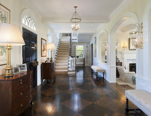 screams sophistication - love the wide hallway, stairs, 2 chests either side of door, benches, arches opening up formal living room