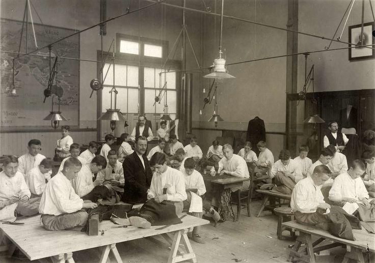 Kleermakers : Leerlingen van de pasgeopende vakschool voor kleermakers in hurkzit aan het werk op tafels die op schragen rusten. Nederland, Utrecht, 1913.