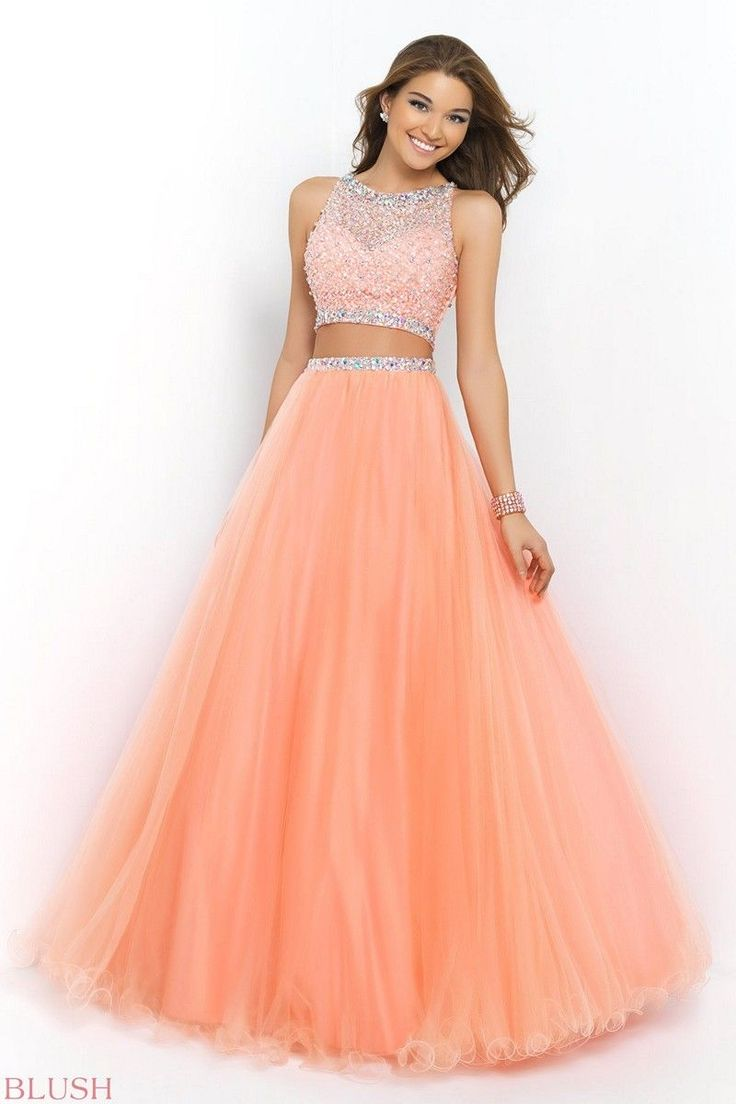 La vie est belle, when you wear this amazing Blush Prom 5400 ballgown. Styled in the latest cropped trend, this two-piece crop top and ballgown skirt set features a sleeveless bodice of crosshatched sequins dotted with AB crystals. Sheer through the decollete and sweetheart lined, the shoulders are taken in while iridescent stones line the edges. The skirt is the real piece de resistance, gathered and full, sitting on the natural waist, and falling to floor length with a curly lettuce…